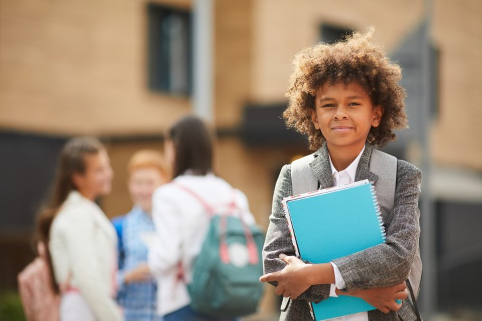 A student wearing a backpack and holding schoolbooks while standing in front of a school.