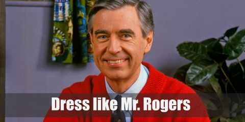 Mr. Rogers is well-known for his comfortable and casual wear. For this outfit, he's wearing a light blue dress shirt, a black patterned tie, a red cardigan, blue pants, and blue sneakers.