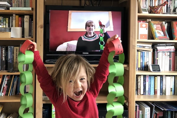 Child playing in front of a TV live stream.