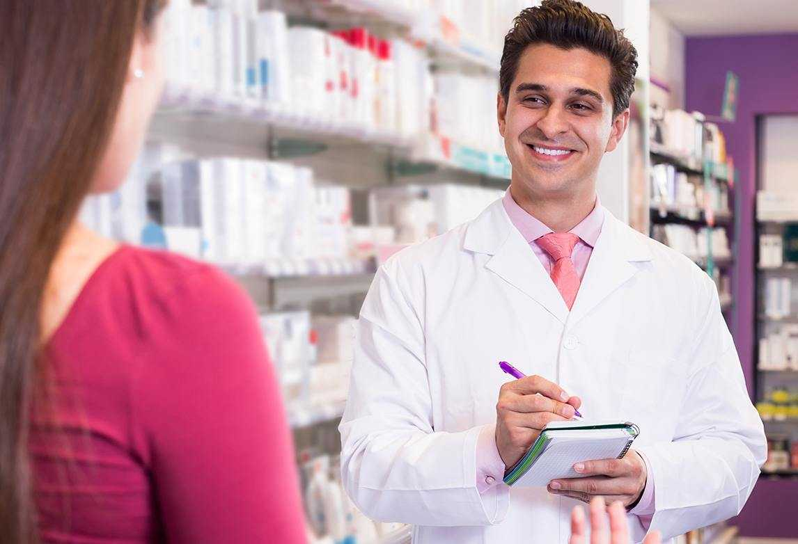 A pharmacy technician interacts with a customer.