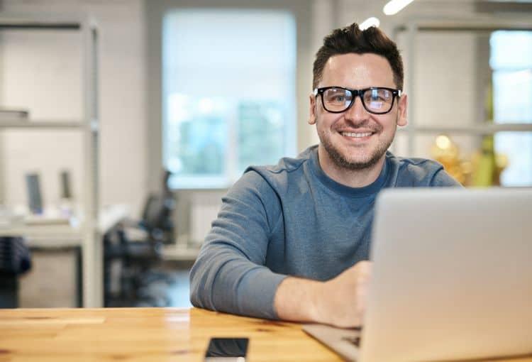 Mann mit Brille im Büro vor Laptop