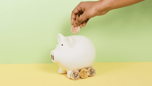 Piggy bank on yellow desk with coins next to it and a hand placing coins into the piggy bank #investment
