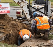 Workers fixing sewer line underground
