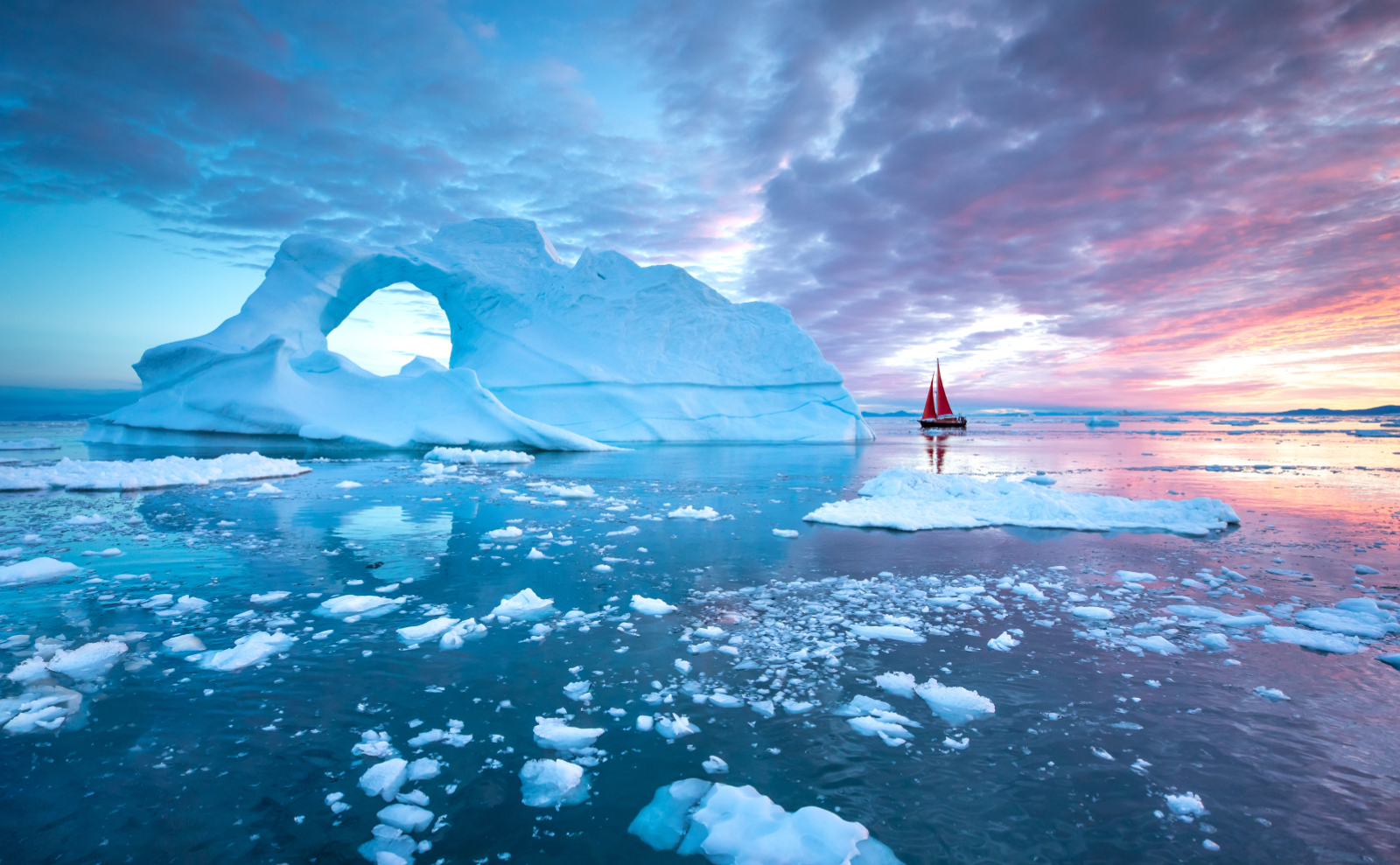a red sailboat bloats next to an iceberg in the arctic