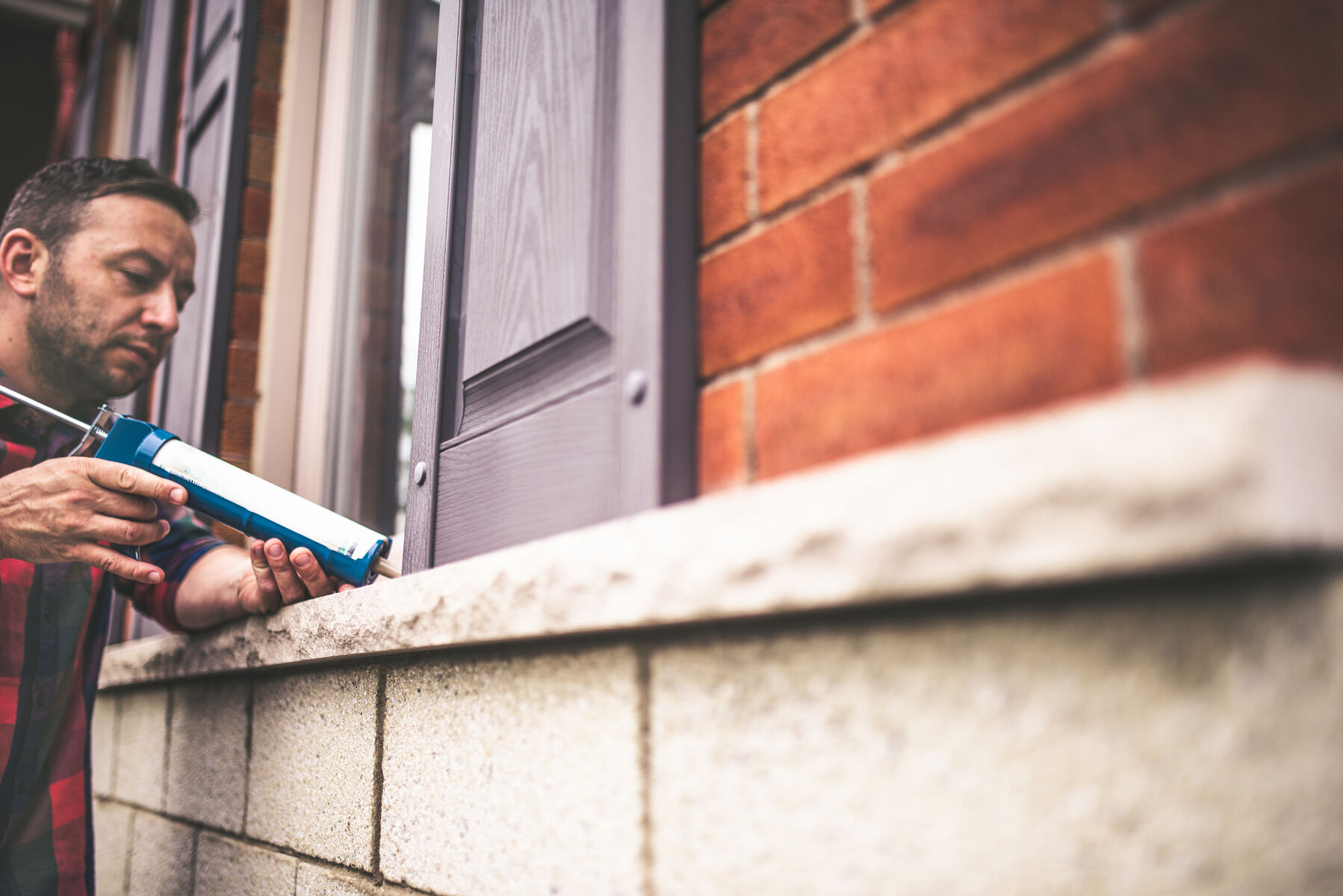 man caulking exterior leaks and cracks on his home with sealant