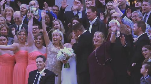 Smiling family surrounding kissing wedding couple
