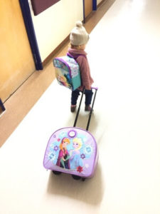 small girl carrying a backpack and wheeler