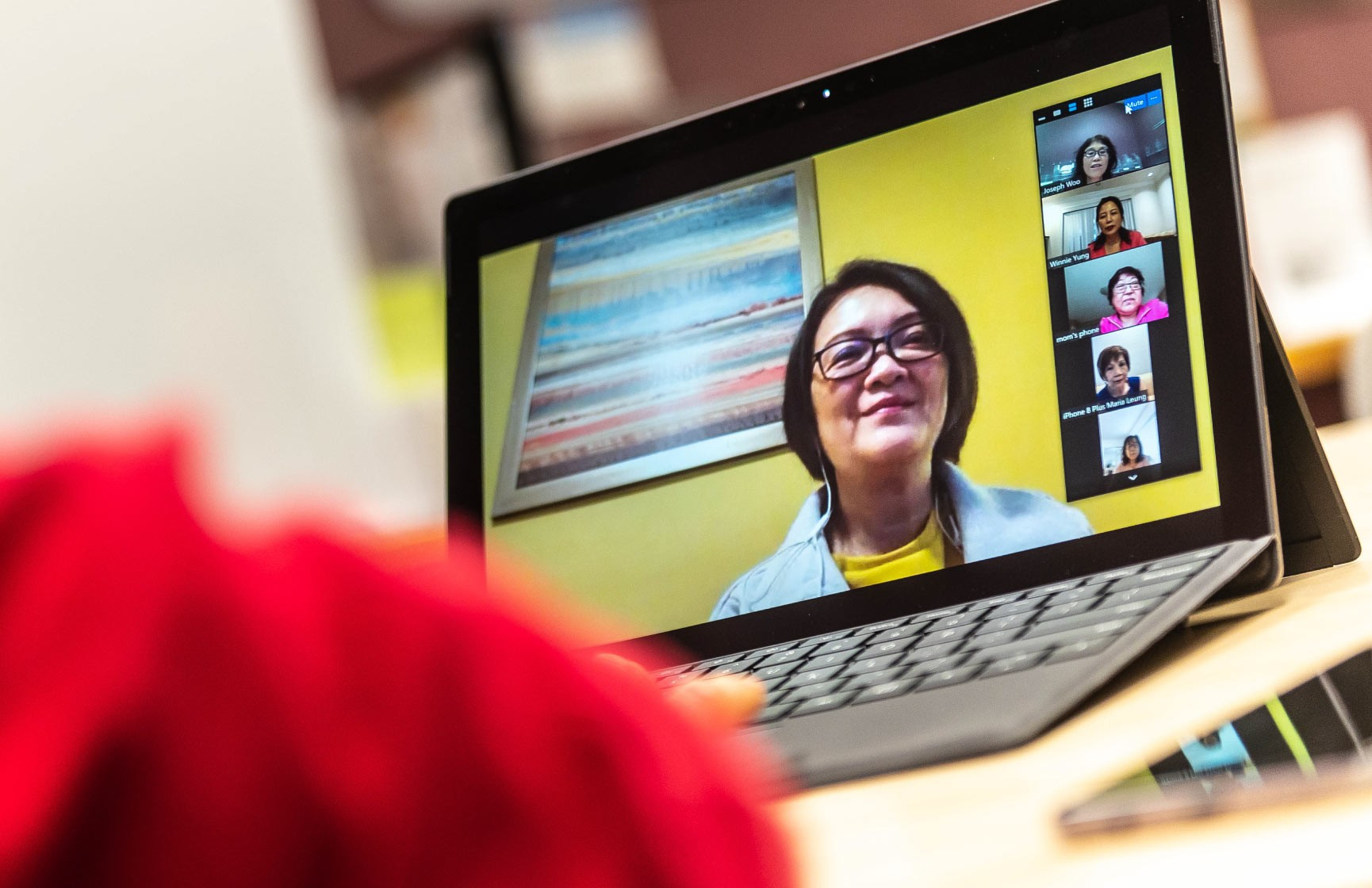 A laptop screen shows a video conference conversation between several seniors