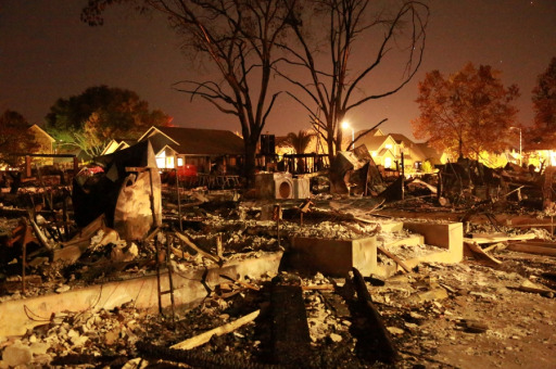 Fire-ravaged neighborhood at night.