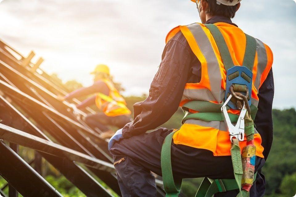 Securite au travail - Un cariste protégé du covid 19 dans un chariot élévateur. Il est  muni d'un gilet jaune, de gants bleus et d'un masque blanc sur le visage.