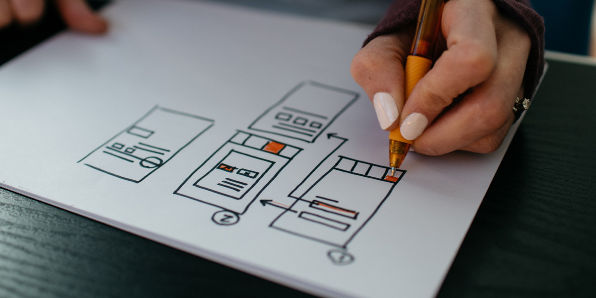 A digital designer wireframing on a piece of paper