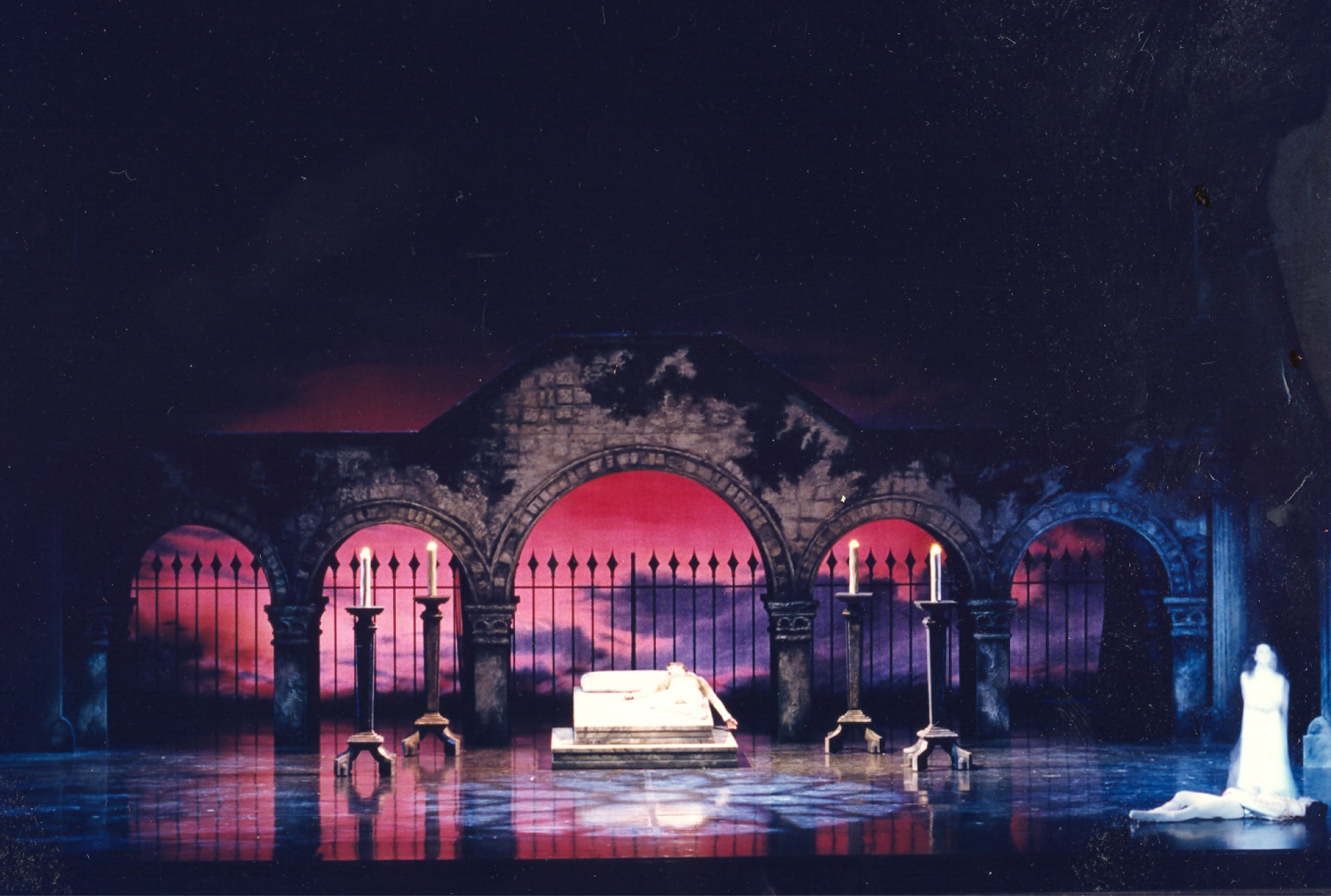 Slain figure lies on bed between tall candles under light from rose window in front of gated bridge against rose-coloured sky.