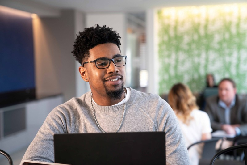 Man in grey sweatshirt and glasses looks up from his laptop as co-workers chat behind him
