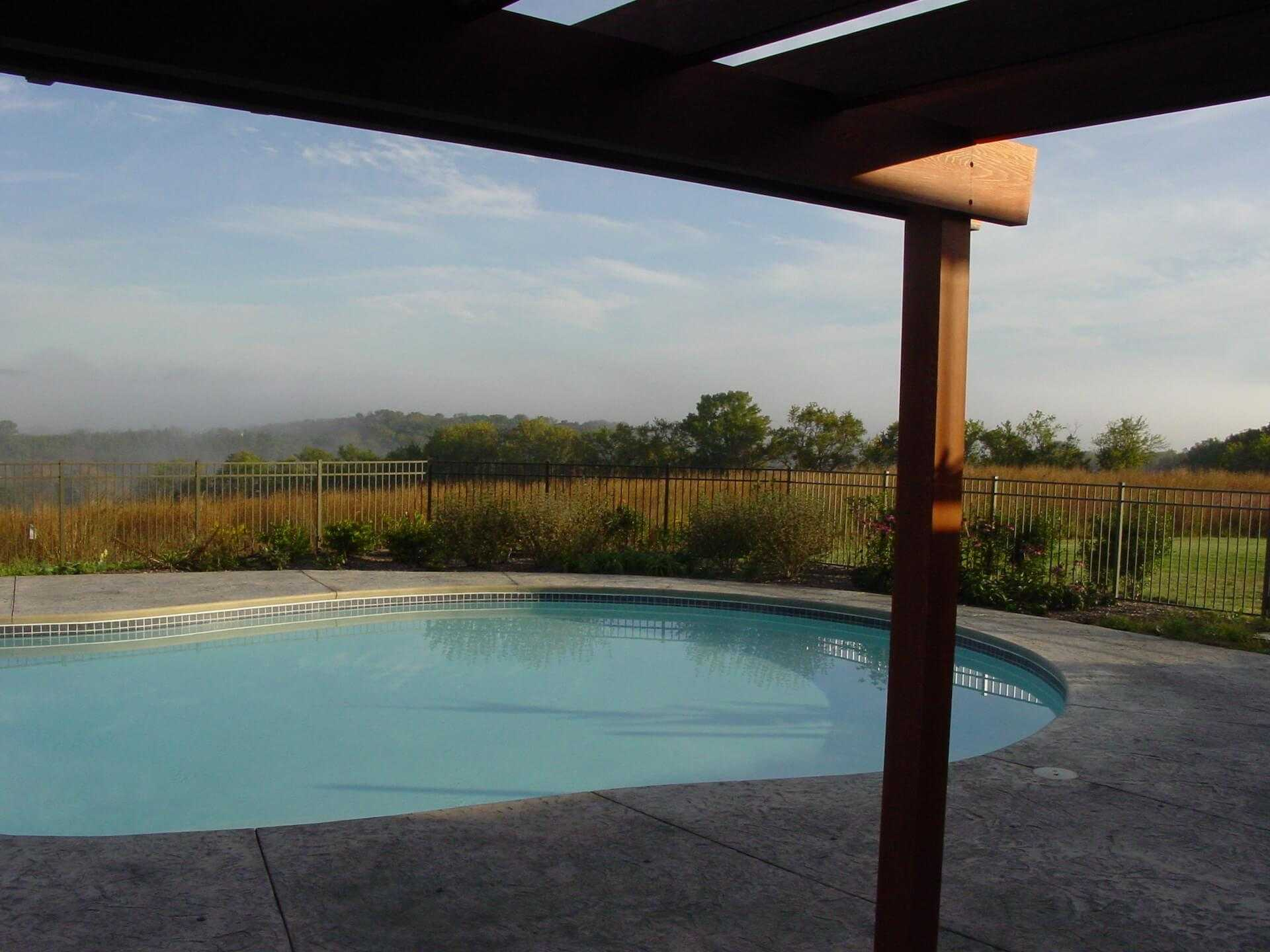 facing out from under the pergola towards the misty meadow