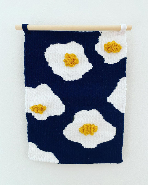 A tapestry featuring fried eggs with fluffy yokes on a navy background