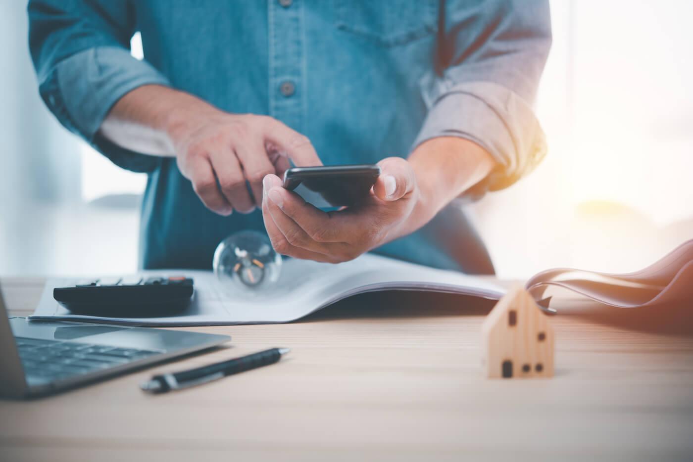 Mann mit Smartphonerechner ermittelt Hauswert