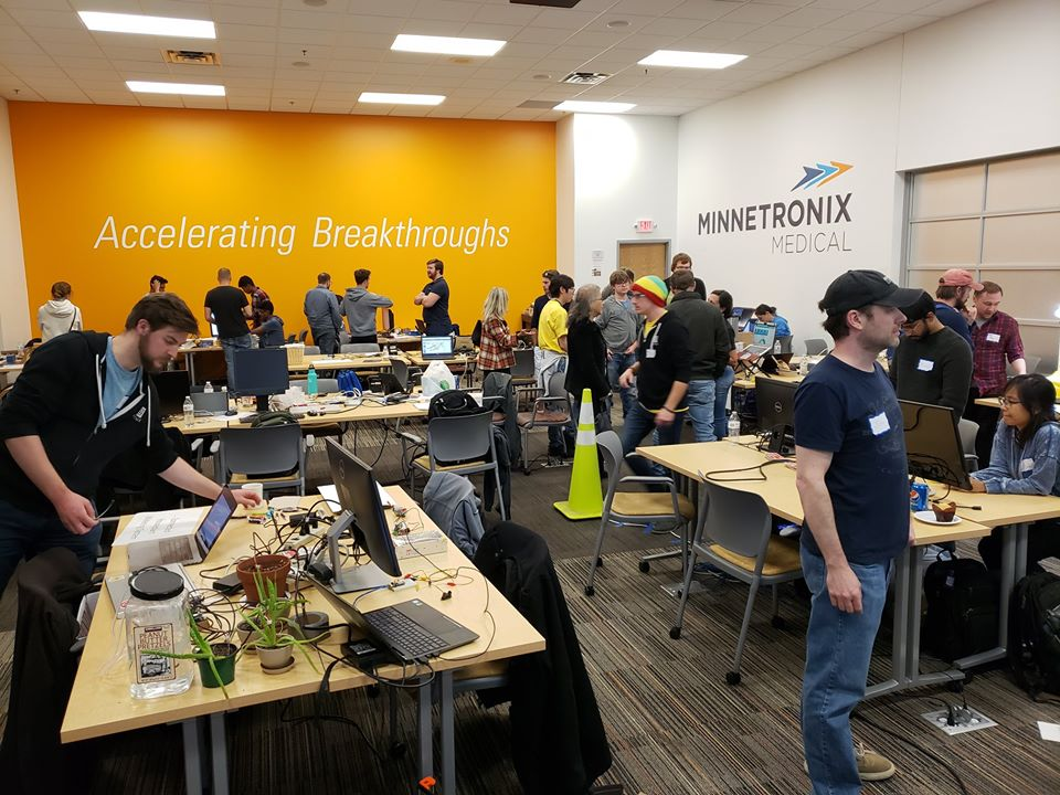 Groups of people at different work tables at IoT HackDay hackathon