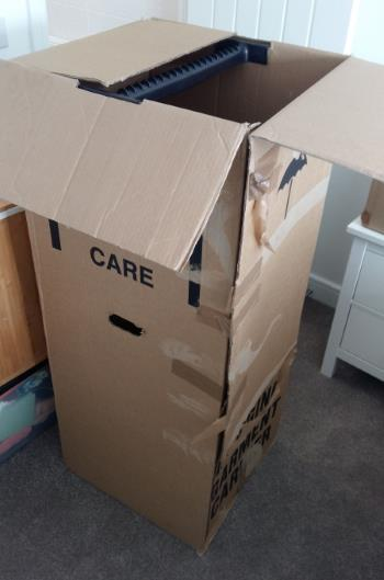 A battered packing box which can be used to store and transport clothes.