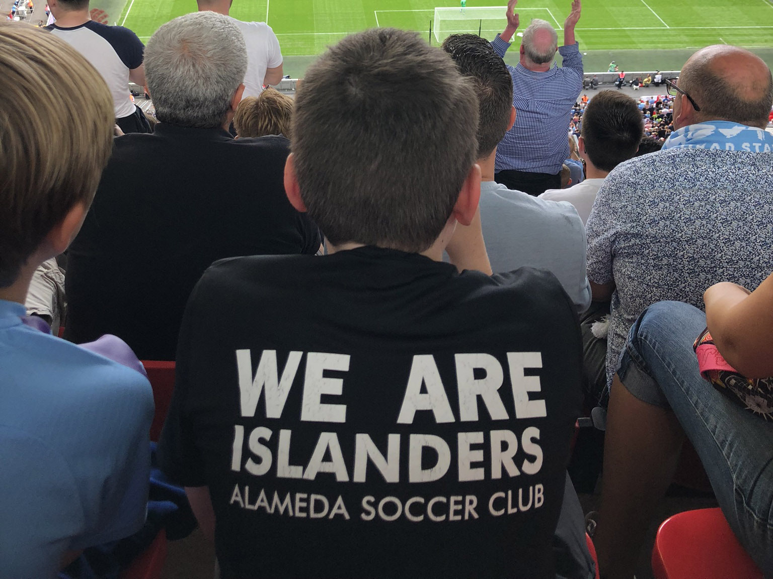 boy wearing T-Shirt saying We Are islanders watching a game