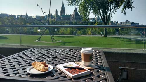 Book, coffee, and snack on a patio table overlooking the Parliament buildings in Ottawa
