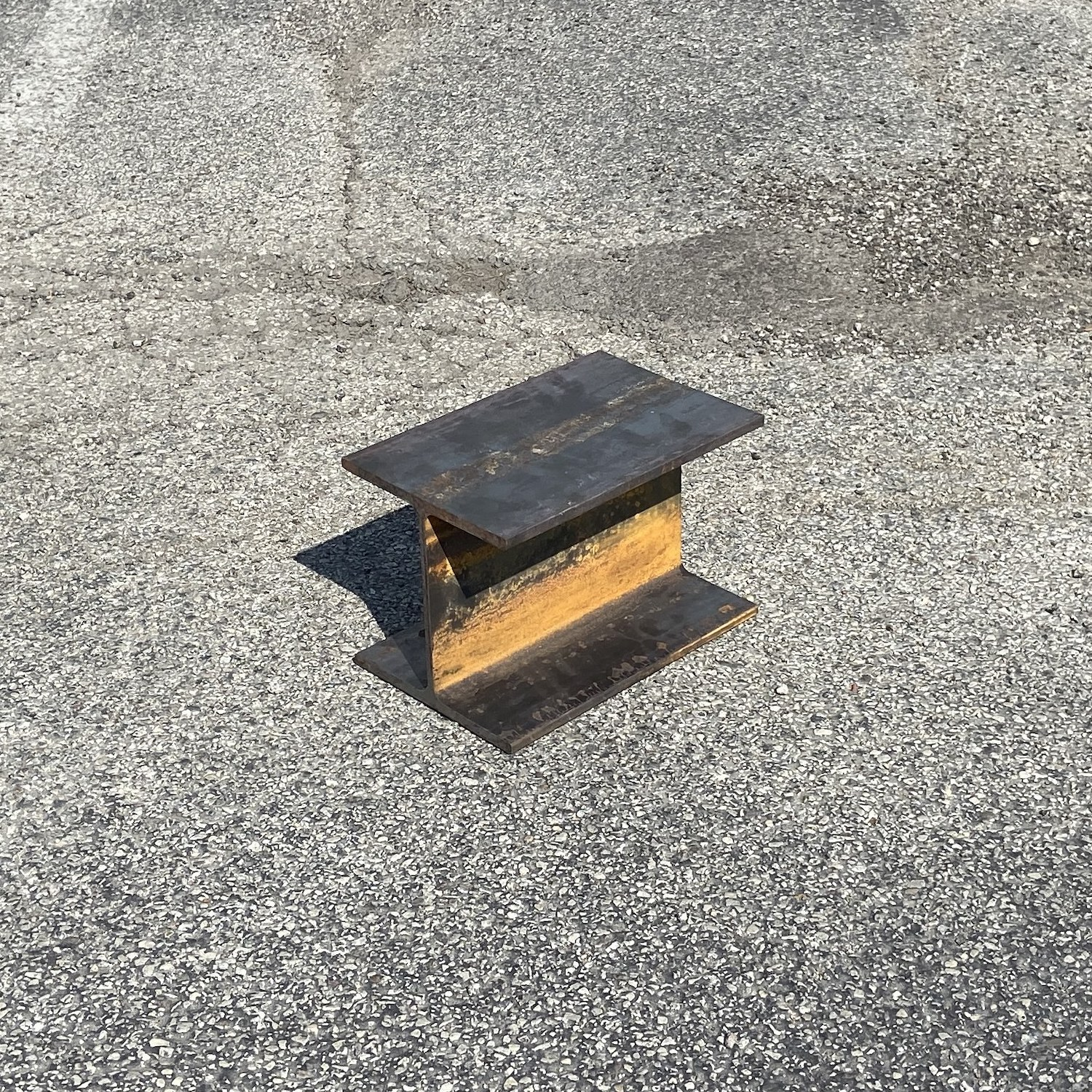 An anvil made out of steel I-beam, photographed in a parking lot.