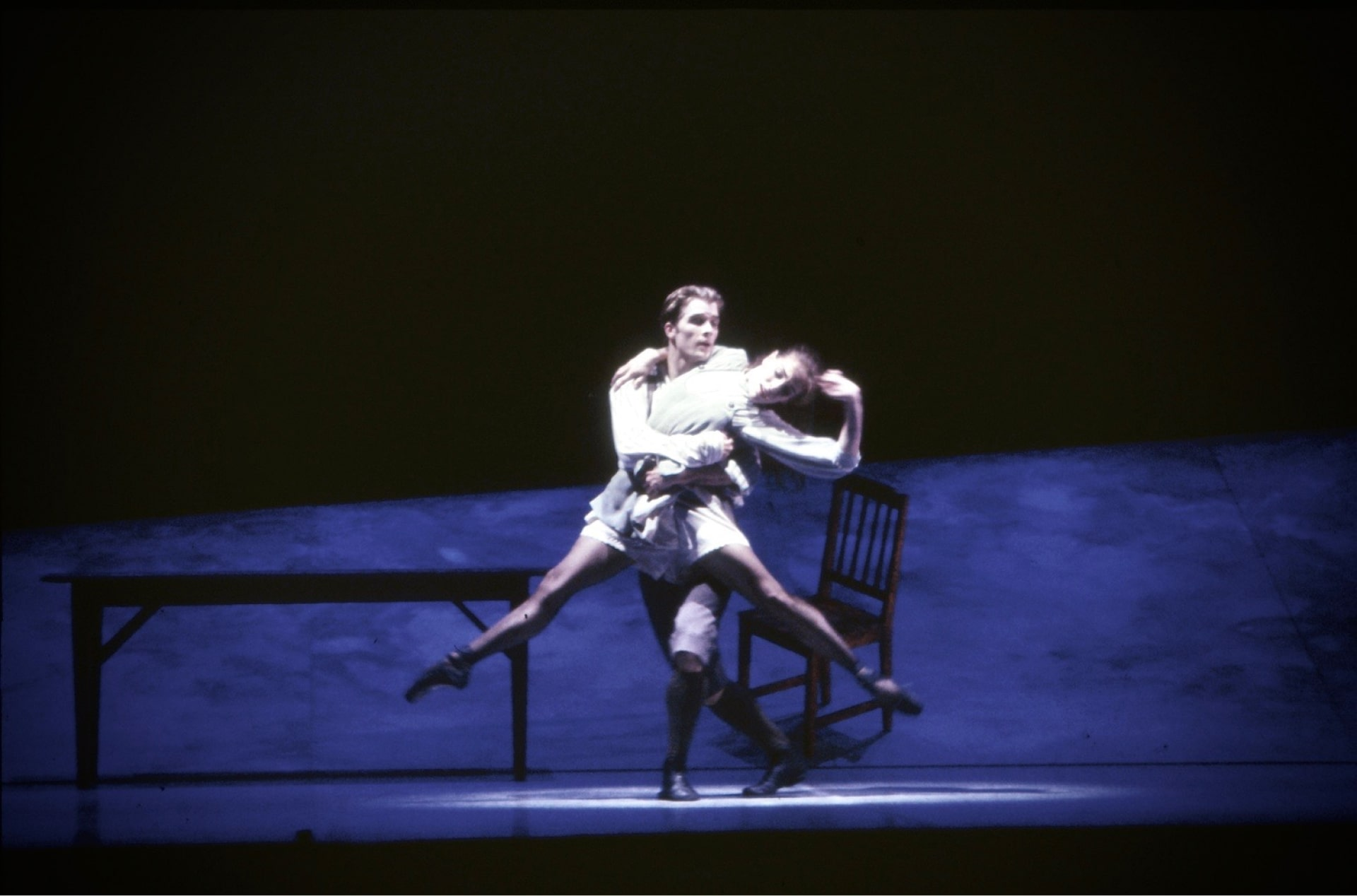 Dancer holds leaping ballerina in front of table, near chair on raked platform.