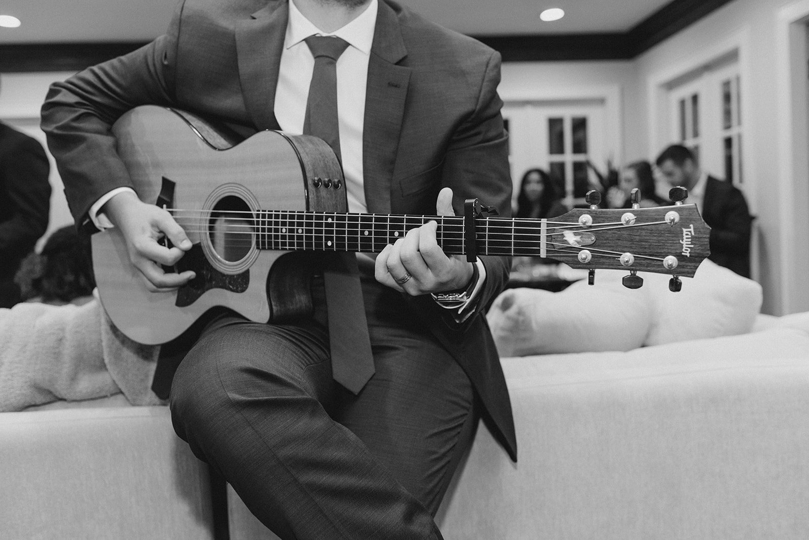Me playing an acoustic guitar while leaning on a couch