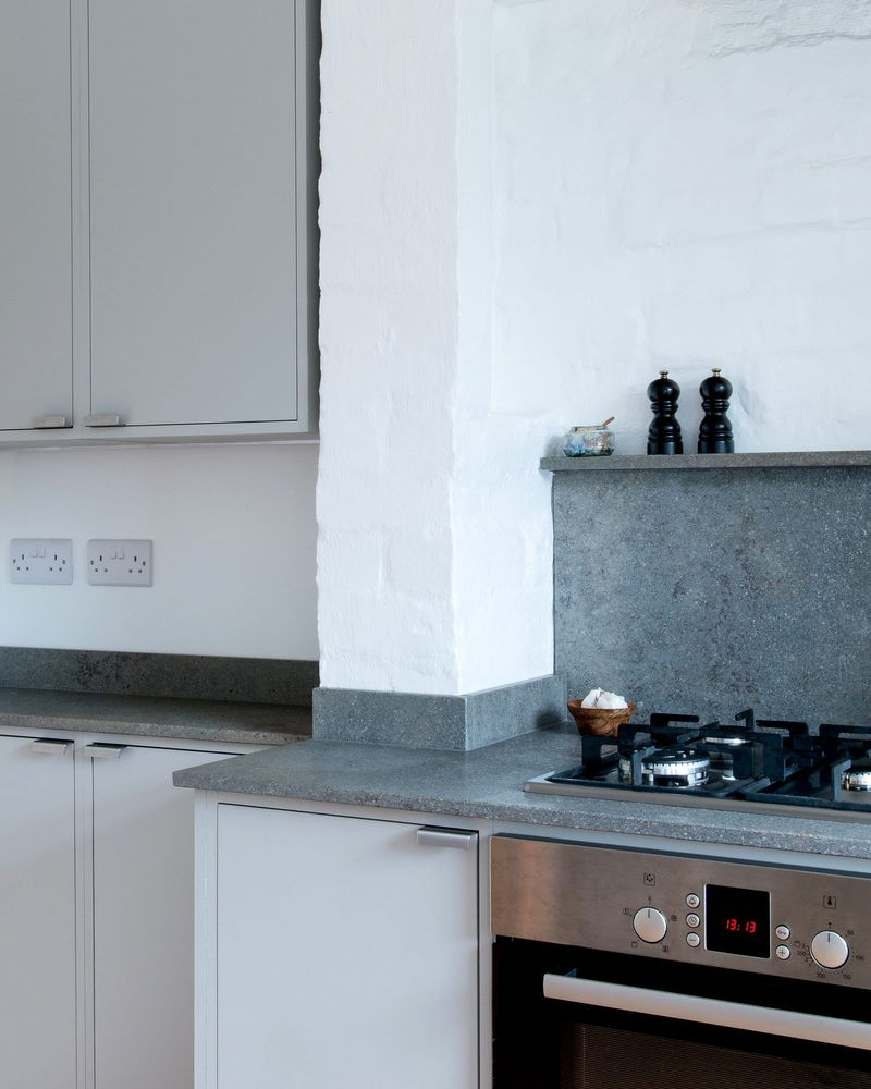 Interior view of the warm grey cabinetry, mandale fossil limestone worktop and cork flooring within the bespoke kitchen in Sheffield designed by From Works.