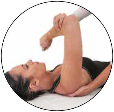 Woman on back having a physio therapist help her with arm stretches