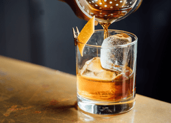 Pouring whisky into glass on ice.