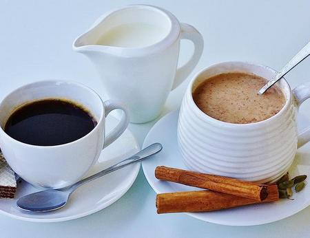 Chai mit Zimtstange und Kardamon sowie Kaffee mit Milchkännchen und Waffel, liebevoll serviert
