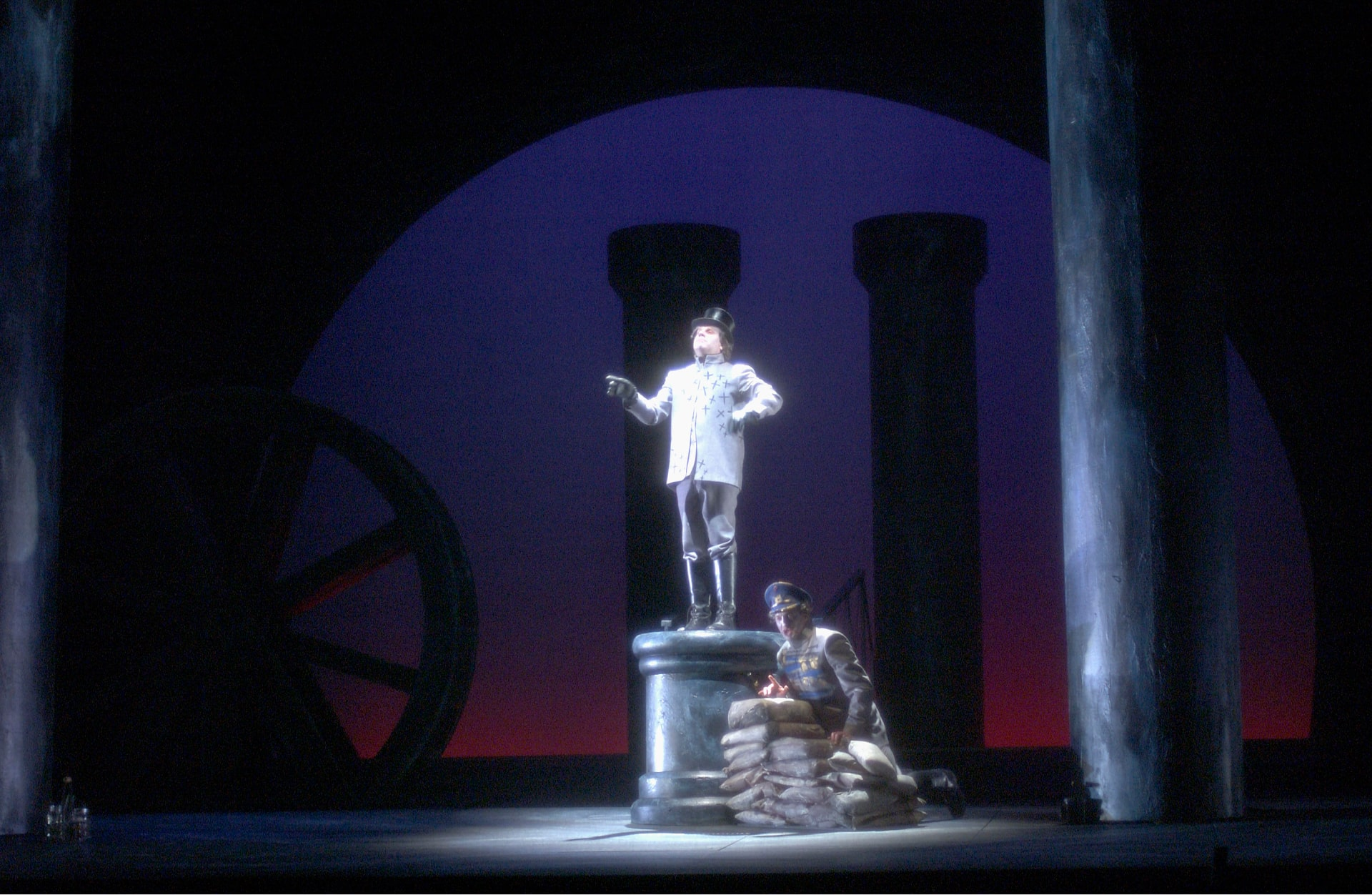 Man in top hat stands on pedestal with soldier crouching on sandbags below, surrounded by columns and backlit by lavender sunrise.
