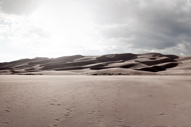 Looking out across a low, even sand field towards a wall of high dunes. Near the center of the image, a group of barely-visible sand boarders drive home the height of the dunes.