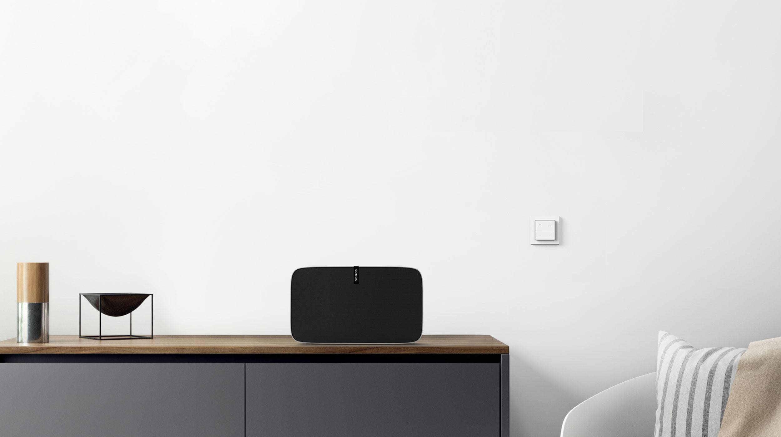 Nuimo Click White fixed on a white wall in a sophisticated living room next to a Sonos speaker and stylish furniture