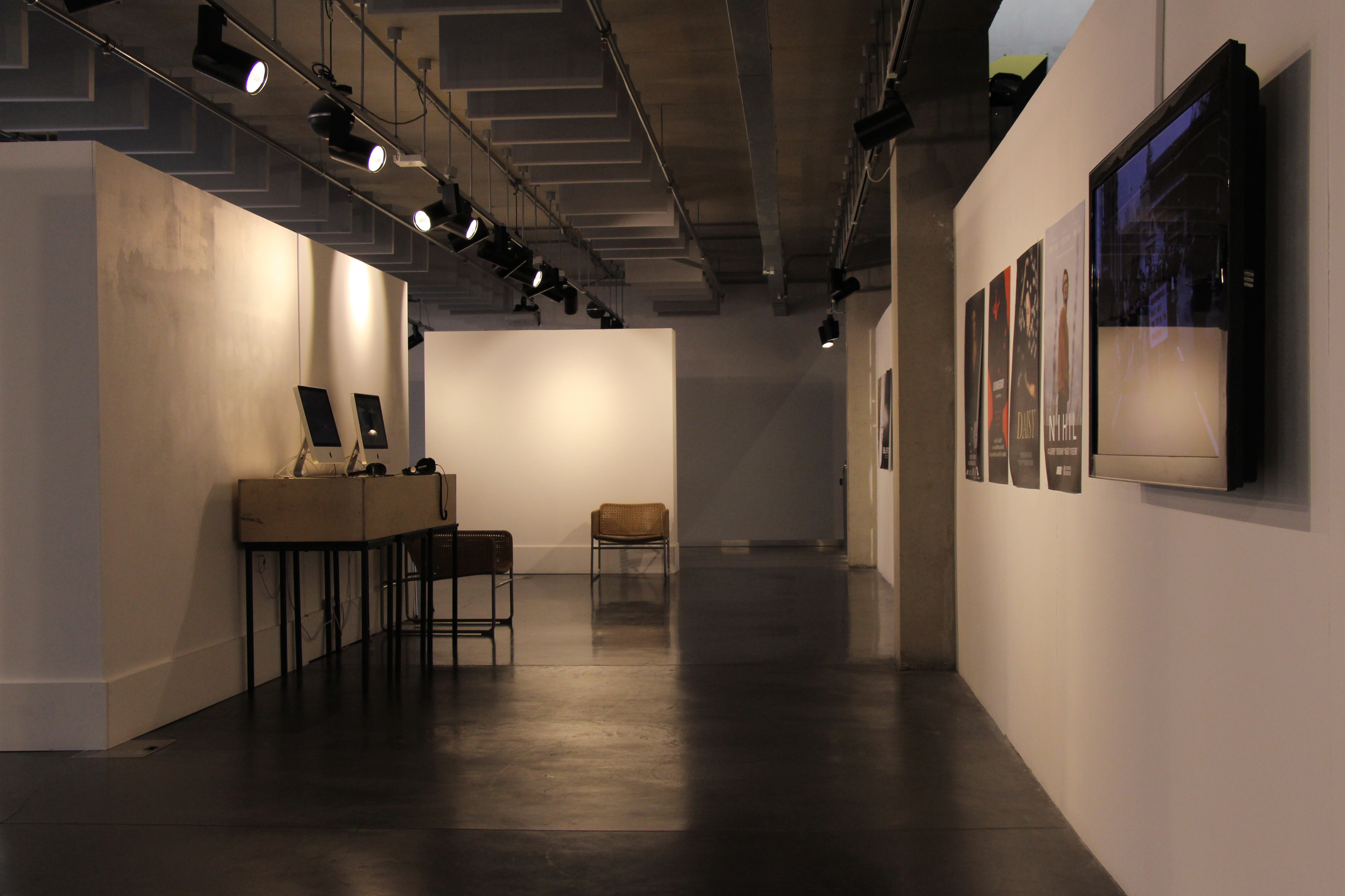 A gallery with posters, a tv screen, and computers installed