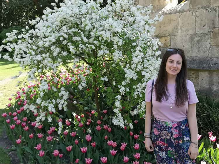 Naomi stood in front of some beautiful pink spring flowers, with a bush flowering with bright white flowers behind her.