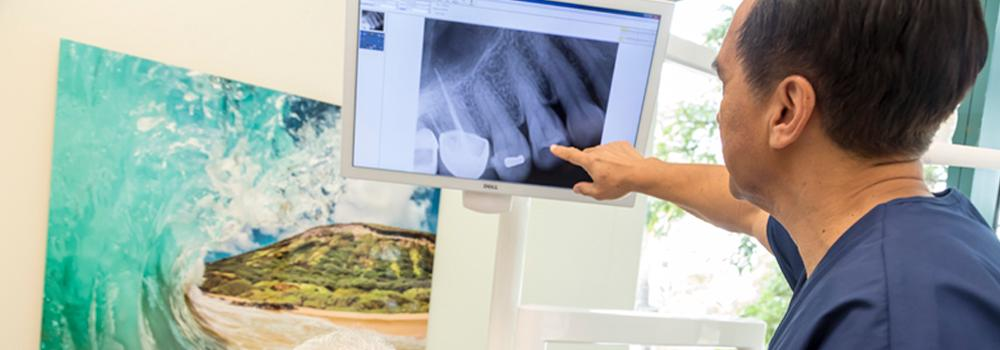 A dentist in his office pointing to an x-ray of teeth.
