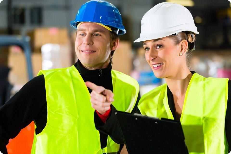 Qualité de vie au travail- 2 employés une femme et un homme, en gros plan souriants, vêtus de gilets jaunes et de casques. La jeune femme tend l'index pour montrer quelque chose, que regarde l'homme avec intérêt..