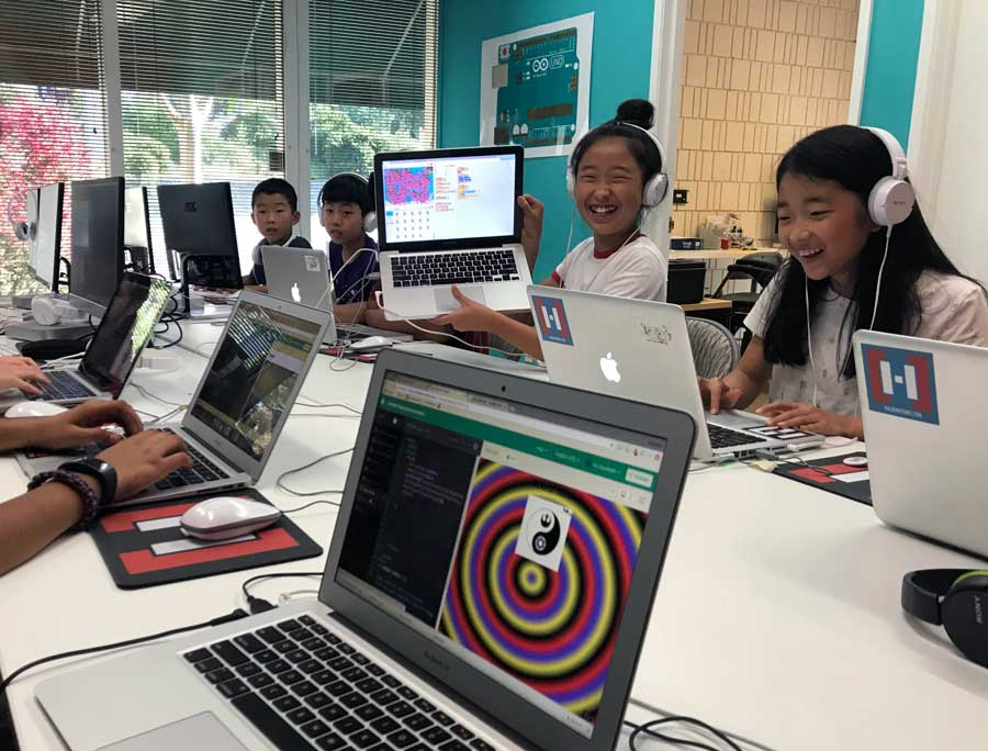 Smiling and laughing female Hackingtons students coding at the Pleasant Hill location.