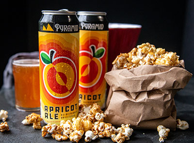 Cans of Apricot Ale next to a bag of caramel corn