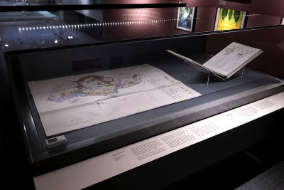 A map of Singapore with several areas highlighted in colour is on display within a showcase.