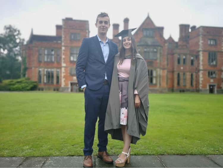 Myself (dressed in a blue suit) and Naomi (in a pink dress and graduation robes) in front of the University of York's Heslington Hall