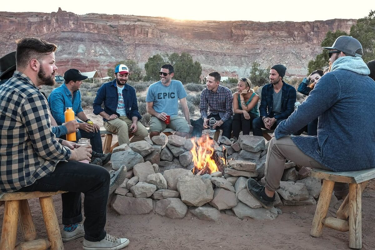 Group of People during vacation telling stories, enjoying and fire in the middle