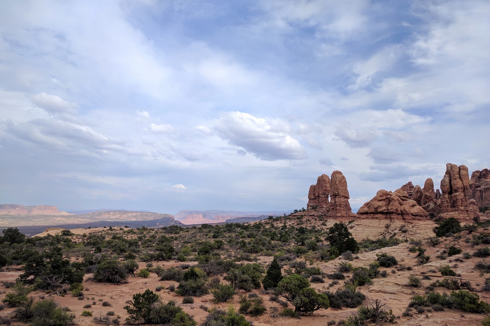 Looking southeast across Arches National Park. Pillars of red sandstone can be seen to the right. In the distance, the walls of a desert canyon almost seem to glow in the Sun's light.