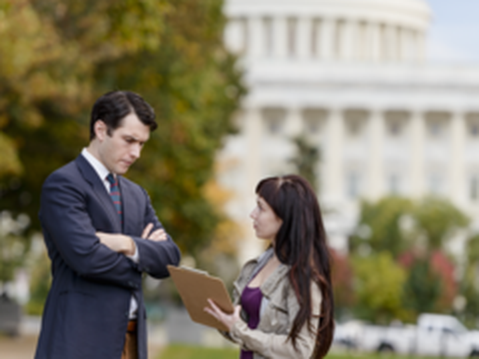 A woman showing a notebook to a man in front of the U.S. Capitol building