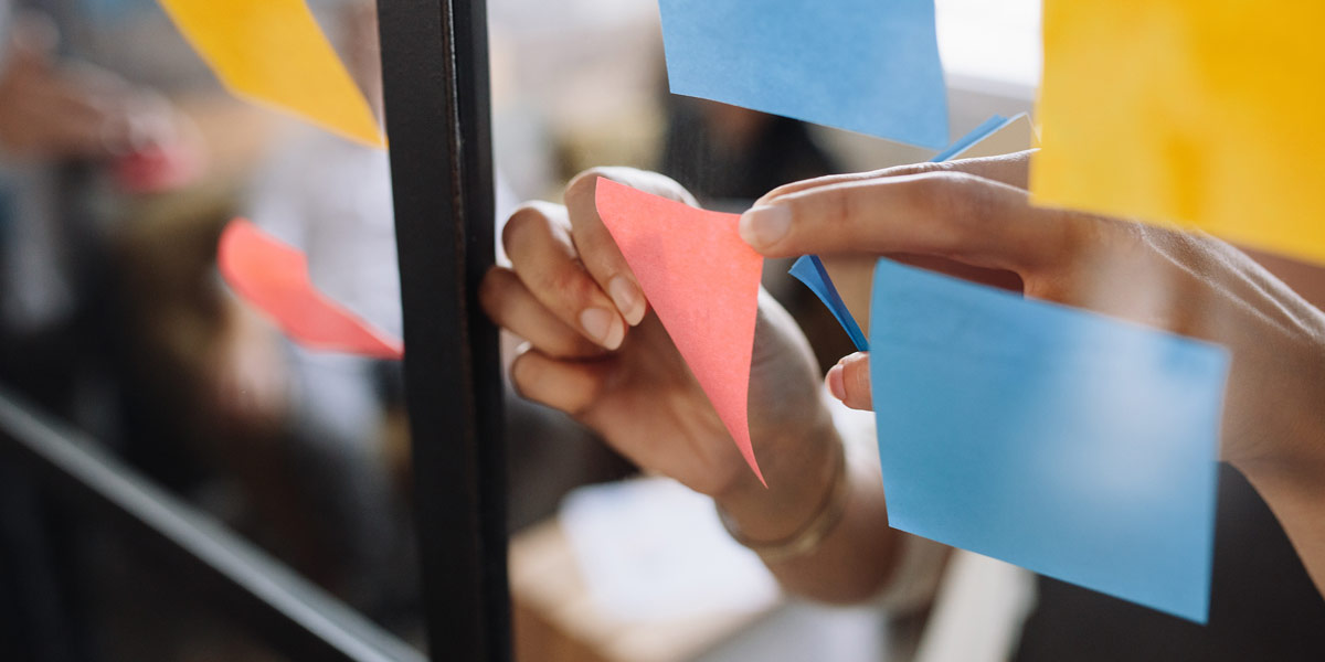 A UX designer arranging Post-It notes on a glass wall
