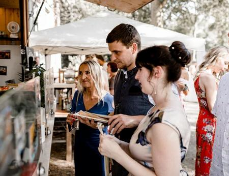 Erwartungsvoll auf Crêpe-Ausgabe wartende Hochzeitsgäste vor mobiler Creperie