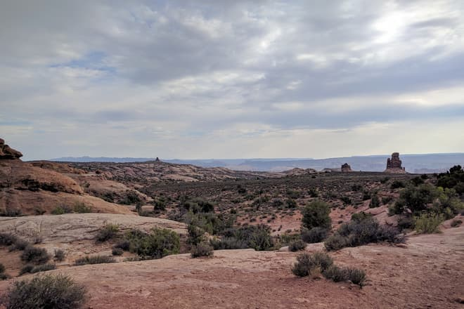 Looking east across Arches National Park. Red and white sandstone undulates across the top of the plateau, with a few stone pillars visible in the distance. On the horizon, the mesas and canyone of Canyonlands National Park.