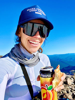 Photo of Morgan Smalley holding a can of Apricot Ale with Mount Rainier in the background