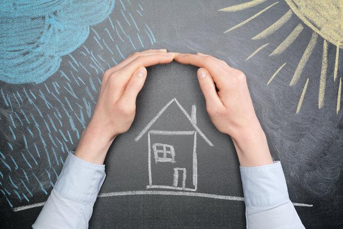 Hände schützen Haus vor Elementarschäden